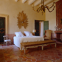 The bedroom has a feeling of faded grandeur with its distressed fireplace and variegated terracotta tiled floor