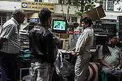 Pedestrians stop to catch a glimpse of the India-Pakistan cricket match at a used electronics shop in Esplanade East in Kolkata, West Bengal, India.