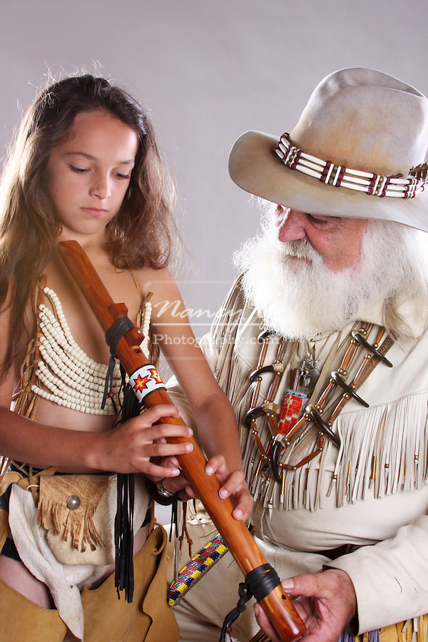 A mountainman teaching a young Native American Indian boy how to play the flute