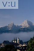 Steeples of St. Andreas and St. Peter as mist clears beneath mountains known as Watzman. Berchtesgaden, Germany