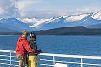 Tourists enjoy mountain views near Juneau Alaska, from the deck of the Matanuska, one of the Alaska State Ferry vessels.