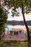 Morning sunrise on a deck bordering a volcano lake at Ndali lodge, Uganda, Africa