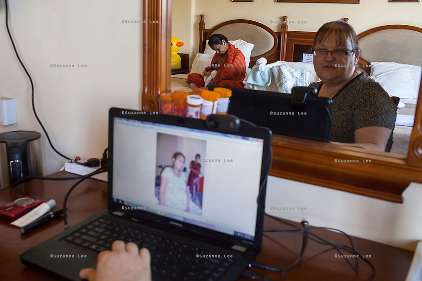 Barbara, from Canada, looks through photographs of her surrogate and baby as her surrogate, Idan, breastfeeds the baby in her hotel room near the Akanksha Clinic in Anand, Gujarat, India on 11th December 2012. Barbara, from Canada, had come to receive him at his birth from Idan, her surrogate, and is waiting for her husband to come and join her in Anand, while she continues to hire Idan to breastfeed her son so that he gets the best start in life. Idan's husband sends pumped breast milk to Barbara's hotel in the evenings when Idan cannot come personally. Photo by Suzanne Lee / Marie-Claire France