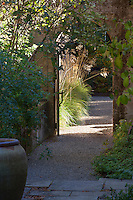 Garden gate entry between shade patio and sunny path with grasses (Stipa gigantea) Gary Ratway garden