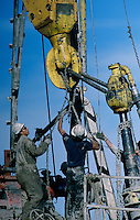 Workers tie down chains on a rotary drilling rig in gas-rich Wyoming. Oil and gas exploration are having a boom in western states.