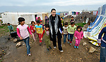 Sabeen Abdulsater (center, in black coat), project officer for the Bekaa Valley for International Orthodox Christian Charities, walks with Syrian refugee children in the village of Jeb Jennine, Lebanon.