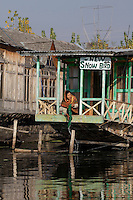 A woman rinses clothes on the porch of a house boat on Dal Lake. Srinagar, Kashmir, India. © Fredrik Naumann/Felix Features