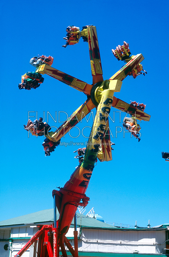 AMUSEMENT PARK RIDES<br /> Spinning Ride<br /> Riders spin in their seats as the big wheel also spins