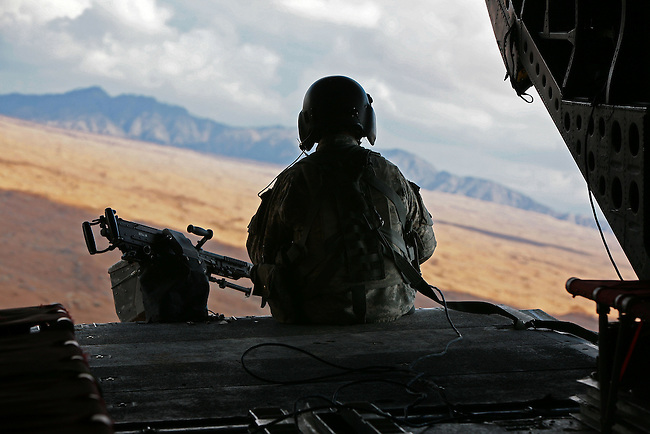 A crew chief sits on the tail ramp of a CH-47 Chinook helicopter as it flies over the Registan Desert, ferrying U.S. soldiers to outlying camps in Kandahar province, Afghanistan. Jan.17, 2009. DREW BROWN/STARS AND STRIPES