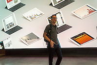 Apple enthusiasts pass a video wall in Williamsburg, Brooklyn in New York at the grand opening of Apple's first store in Brooklyn on Saturday, July 30, 2016. The tech company's new store features exposed brick, giant arch windows and at one story with a brick facade blends in with the neighborhood. Apple gave away commemorative tee-shirts to those attending the grand opening. (© Richard B. Levine)