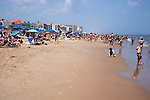 Crowds pack the beach and children play at the water's edge on a hot summer day at Rehoboth Beach, Delaware, USA.