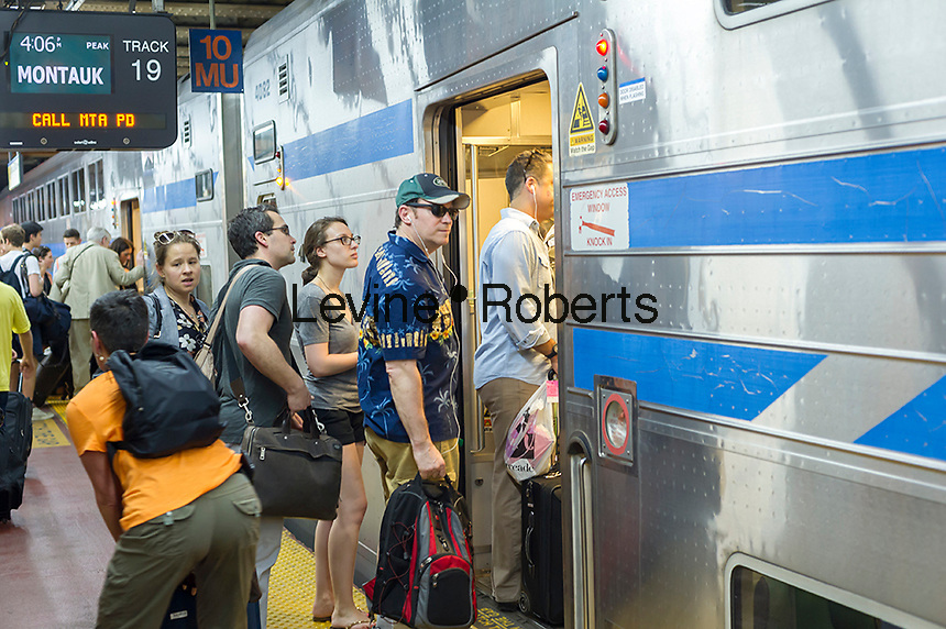 Thousands pack the Cannonball at Penn Station in New York to get out of the city for the Memorial Day weekend on Friday, May 27, 2016. Every Friday during the summer the train, consisting of double-decker cars pulled by a powerful dual-mode locomotive, will run express to Westhampton on Long Island making the 76 mile trip in 94 minutes. From Westhampton it will continue to points east arriving at the tip of the island, Montauk. On Sundays the train will reverse and return to Penn Station. The train is the only named run on the railroad. The trip from Penn Station to the Montauk terminal is 117 miles making the train the longest run on the railroad. (© Richard B. Levine)