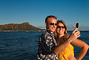 Young adult couple taking photos of themselves with cell phone camera with Diamond Head in the background; Waikiki Beach, Oahu, Hawaii.