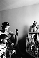 "USA. New York City. Spanish Harlem. Nina has put one's hair in rollers and seats on her bed with her younger son Papo. A religious statue is on the sideboard close to a photo and a fan. The Puerto Rican family lives below the poverty line and receives public assistance (AFDC, Home Relief, Supplemental Security Income and Medicaid). The family resides in units managed by the New York City Housing Authority (NYCHA) which provides housing for low income residents. NYCHA administers rental apartments in facilities, popularly known as ""projects"". Spanish Harlem, also known as El Barrio and East Harlem, is a low income neighborhood in Harlem area. Spanish Harlem is one of the largest predominantly Latino communities in New York City. 30.06.88 © 1988 Didier Ruef ."