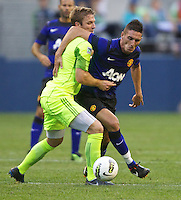 Seattle Sounders FC defender Jeff Parke, left, battles Manchester United forward Federico Macheda during play at CenturyLink Field in Seattle Wednesday July 20, 2011. Manchester United won the match 7-0.