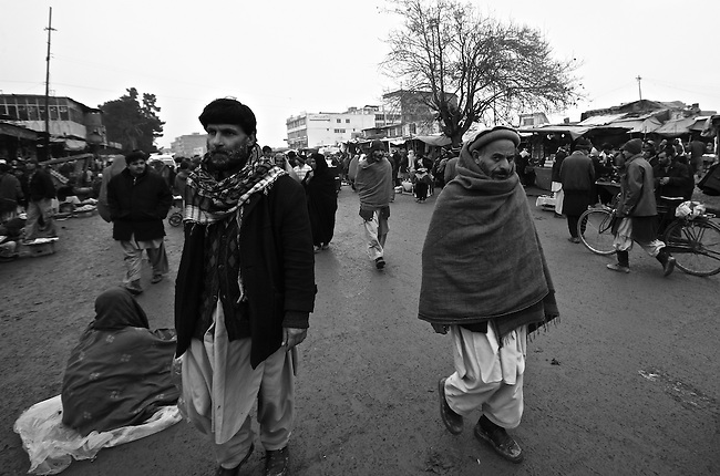 Men walk through the central market of Kabul, Afghanistan. Despite the ever-present mud and miserable winter weather, the market bustles daily with commerce of all kinds. Taliban attacks in the Afghan capital have so far been infrequent, and as life goes on at a normal pace, the war often seems far away. Feb. 3, 2009.