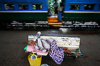 An ill woman rests at the Yangon's central station as a circular train leaves September 17, 2012. Around Yangon, with its growing and increasingly demanding population of almost five million, a circular train operates moving passengers through its suburbs. On a three hour long ride, a train made of rusted vehicles marked with different classes but little difference between them, takes passengers around the city stopping briefly on numerous small stations.    REUTERS/Damir Sagolj (MYANMAR)