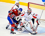 10 February 2010: Montreal Canadiens' left wing forward Mathieu Darche (52) is checked by Washington Capitals defenseman Mike Green as goaltender Jose Theodore tries to keep an eye on the play at the Bell Centre in Montreal, Quebec, Canada. The Canadiens defeated the Capitals 6-5 in sudden death overtime, ending Washington's team-record winning streak at 14 games. Mandatory Credit: Ed Wolfstein Photo