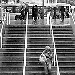 People with umbrellas and a woman walking down stairs at Burrard Station.