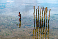 July 1987, Biak, Indonesia --- A naked young boy fishes with a pointed stick near a row of wooden pilings. Biak Island, Schouten Islands, Indonesia. --- Image by &copy; Owen Franken/CORBIS - Photograph by Owen Franken