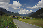 Alpine meadows homes and farm buildings, looking towards snow capped mountains and town of Tarrenz. Imst district, Austria.