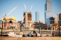 A couple basks in the late afternoon sun on the High Line Park with construction of the Hudson Yards development behind them,  in New York on Friday, October 14, 2016.  (© Richard B. Levine)