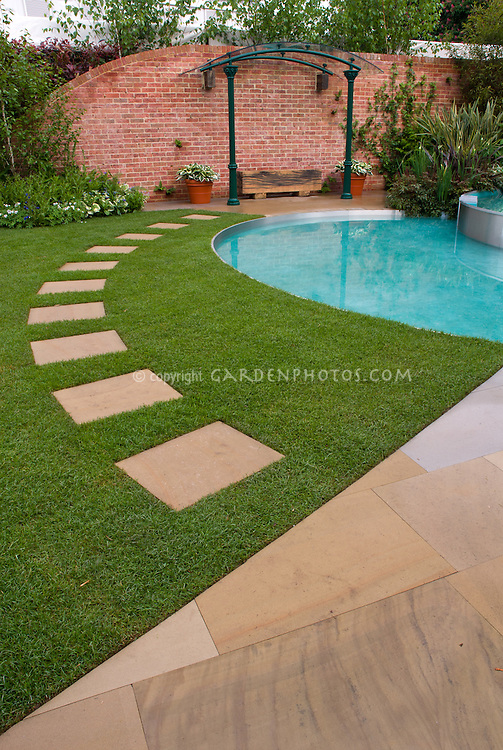 Walkway through lawn near patio and pool water