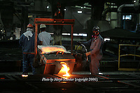 A worker at D & L Foundry in Moses Lake, Washington pours an iron mixture into manhole-cover molds on August 16, 2006. His gloves and protective suit are designed to insulate his hands, lower arms and body from temperature extremes and hot splashes fro molten metals or other hot liquids. He is also wearing a Class B hard hat, earplugs and respirator.