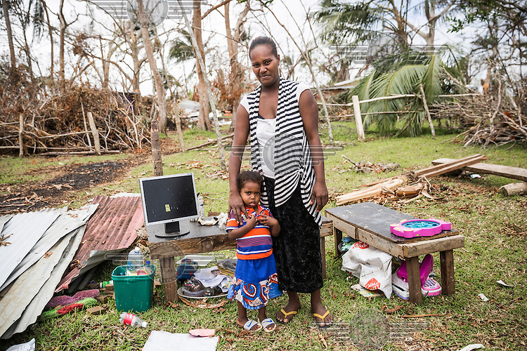 Lydia Kalsakau, 26, with her three year old daughter Luisa, standing beside the remaining teaching aids rescued from the ruins of St Martin's kindergarten which was destroyed by Cyclone Pam on 13 March 2015. Lydia, who lives close to St Martin, was due to give birth to her second daughter on the night of the Cyclone. She says: 'We took shelter at a friend's house. I was very afraid that the house will collapse and I can loose my family and my unborn child. But the walls of the house were strong enough. Two days after the Cyclone I gave birth to my second daughter. Now I came to help teacher to rebuild the kindy so that kids from our village start to go to pre-school again.'