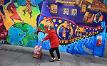 A woman returning from the farmers market in the Civic Center strolls up a hill with a colorful mural to accent her colorful red coat and matching shopping cart in Tenderloin district of San Francisco, California.