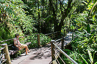 A visitor relaxes in the shade on the boardwalk at the Hawai'i Tropical Botanical Garden in Onomea, a 4-mile scenic drive north from Hilo on the Big Island of Hawaiʻi.