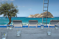 A row of white deck chairs positioned on the beach side terrace to admire the view of the breaking waves