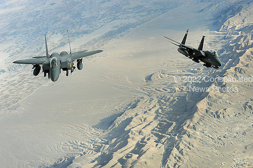 """Over Afghanistan - November 8, 2008 -- Two F-15E Strike Eagles fly a mission over Afghanistan on Tuesday, October 7, 2008. The aircraft uses two crew members, a pilot and a weapon systems officer. Previous models of the F-15 are assigned air-to-air roles; the """"E"""" model is a dual-role fighter. It has the capability to fight its way to a target over long ranges, destroy enemy ground positions and fight its way out. .Credit: Aaron Allmon - USAF via CNP"""