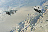 "Over Afghanistan - November 8, 2008 -- Two F-15E Strike Eagles fly a mission over Afghanistan on Tuesday, October 7, 2008. The aircraft uses two crew members, a pilot and a weapon systems officer. Previous models of the F-15 are assigned air-to-air roles; the ""E"" model is a dual-role fighter. It has the capability to fight its way to a target over long ranges, destroy enemy ground positions and fight its way out. .Credit: Aaron Allmon - USAF via CNP"