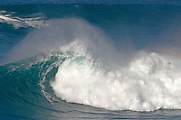 A surfer comes to the end of his Hawaiian big surf ride while his tow-in partner rides to next wave to pick him up at Peahi (Jaws) off Maui.