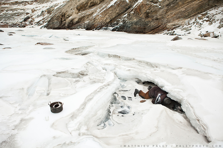A caravan leader looks for water under the thick sheets of ice covering the Wakhan river. No luck: he will have to melt snow for his tea...Shepherd place names Kher Metek...Going back down to Sarhad village with a yak caravan led by 2 Wakhi traders: Shur Ali and Roz Ali...Trekking down the Wakhan frozen river, the only way down to leave the high altitude Little Pamir plateau, home of the Afghan Kyrgyz community.
