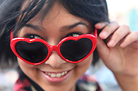 A young girl smiling and wearing heart shaped sunglasses.