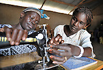 Besta Kide learns about sewing from Rehema Ajiba Asga, who teaches classes in a community center in Mugwo, in Southern Sudan. The skills training program is sponsored by the United Methodist Committee on Relief (UMCOR).