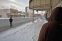 Detroit: paesaggio urbano. Una strada della città innevata. Due persone e qualche negozio.
