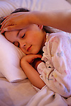 Young girl ( 7 years old) in bed with flu/cold with mother feeling her forehead for a temperature and comforting her.   MR.