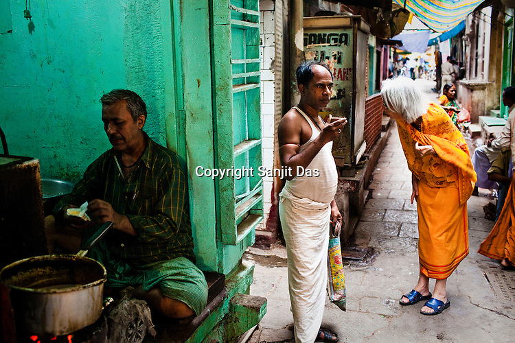 A foreigner dressed like a sadhu (holy man) looks for a street while a man is seen drinking his tea in the narrow alleys of the ancient city of Varanasi in Uttar Pradesh, India. Photograph: Sanjit Das/Panos