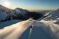 Mountaneering alpine shelter, Almer Hut in upper parts of  Franz Josef Glacier at winter sunset with Tasman Sea on horizon, Westland Tai Poutini National Park, West Coast, UNESCO World Heritage Area, New Zealand, NZ