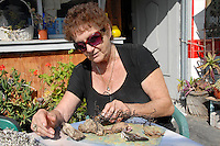 Artist and owner of the Infinity Art Studio , Susan Weinberg, works on her environmental art piece at Ocean Front Walk  on Thursday, April 14, 2011. The art piece is made from seashells and other organic items gathered from the shoreline.