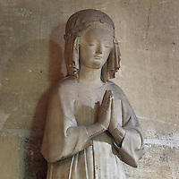 Stone statue of Isabella of France, 1225-70, younger sister of Saint Louis or Louis IX, as a young girl at prayer, in the Collegiale Notre-Dame de Poissy, a catholic parish church founded c. 1016 by Robert the Pious and rebuilt 1130-60 in late Romanesque and early Gothic styles, in Poissy, Yvelines, France. Saint Louis was baptised here in 1214. The Collegiate Church of Our Lady of Poissy was listed as a Historic Monument in 1840 and has been restored by Eugene Viollet-le-Duc. Picture by Manuel Cohen