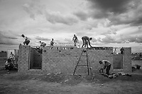 Kakuma, Kenya: Men working on the ISSB (Interlocking Stabilized Soil Bricks) project are in the final stages of construction on this house, which will eventually house Somali refugees from Dadaab camp who have been resettled here pending their ultimate resettlement in the United States. A house can be built in as little as a day using the ISSB technology, which foregoes traditional brick and mortar for a LEGO-like construction method.