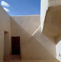 The smooth walls of this village dwelling are made in the traditional way using a mixture of sand, small stones and straw, painted off white to reflect the sun