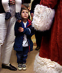 Devon Myers, 3 1/2, stares up at Santa witha mixture of fear and awe during feativities at Sacramento Elementary School for their Santa breakfast. Devon followed him throughout the morning eventually getting close enough to make sure his beard was real.
