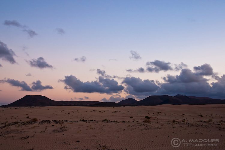 Desert and dunes, Fuerteventura, Canary Islands, Spain. Over the centuries, the winds coming from Africa carried sand from the Sahara and dropped it on the east coast of Fuerteventura. A large area of the island, near Corralejo, resembles a small desert. Since 2009 the whole island is considered a Biosphere reserve by the UNESCO.