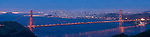 San Francisco, California; a panoramic view of the Golden Gate Bridge and the San Francisco skyline in lights just after sunset