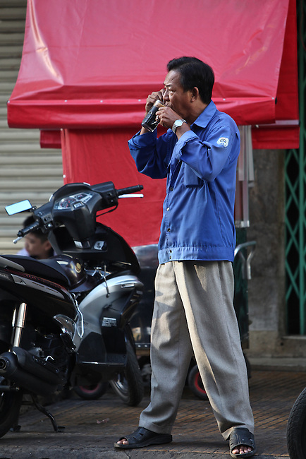 A motorbike taxi driver has morning coffee on Bui Vien Street in Ho Chi Minh City, Vietnam. Aug. 18, 2011.